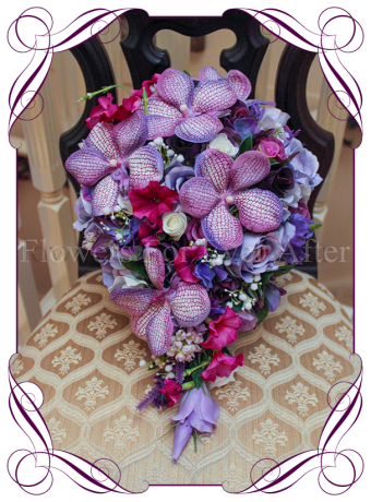 A colourful tear bridal bouquet filled with various pink and purple blooms. A unique collection of silk artificial flowers designed in a classic and elegant shape.