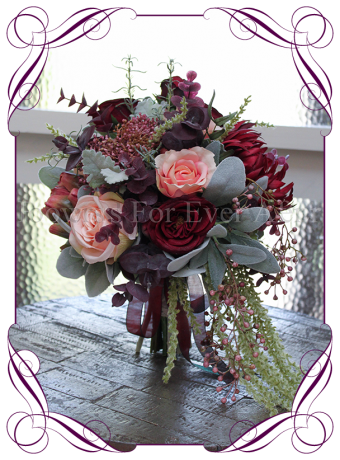 A unique silk bridal bouquet with unusual artificial wedding flowers in burgundy, coral and pink. A very rustic and uneven style with bold dahlia, berries and roses. Suitable for rustic, whimsical or bohemian weddings.