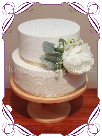 White cake flowers / decoration made with artificial foliage, baby's breath and white silk peony.