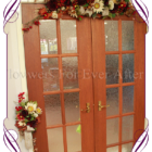 Fall / Autumn theme silk wedding arbor / arbour decoration. Fake wedding arch decoration. A thick garland or artificial blooms and berries in deep Autumn / fall tones.