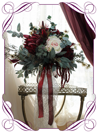A large silk bridal bouquet with with the high quality artificial wedding flowers in burgundy and ivory, with Australian native leaves.