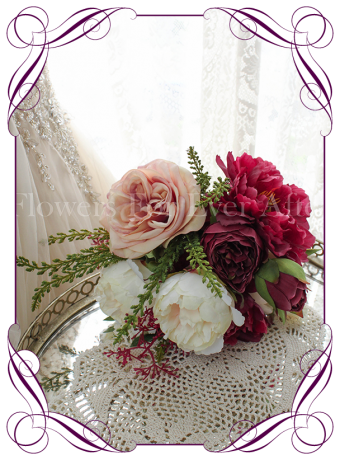An elegant unusual silk artificial bridesmaid bouquet design with peonies and roses in raspberry, ivory and champagne apricot. Made in Melbourne. Worldwide shipping.